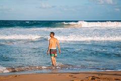 Jonge mens die in reusachtige golven zwemmen stock foto