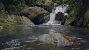 Jonge mens die in rivierstroom zwemmen die van waterval in het tropische bos Reizende mens baden in watervalrivier stromen stock video
