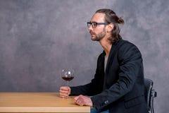Jonge mens die rode wijn drinkt Royalty-vrije Stock Foto's