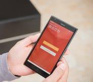 Jonge mens die rode zak op mobiel op WeChat voor Chinees nieuw jaar voorbereiden Stock Afbeeldingen