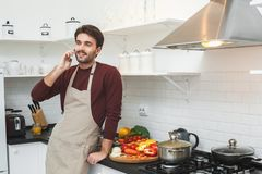 Jonge mens die romantisch diner koken die thuis gebruikend smartphone spreken royalty-vrije stock afbeeldingen