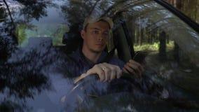 Jonge mens die rond het drijven van auto langs boskant op de zomerdag en gebruikssmartphone kijken stock footage