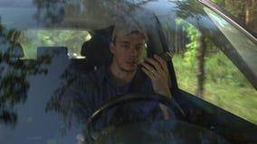 Jonge mens die rond het drijven van auto langs boskant op de zomerdag en het spreken op de telefoon kijken stock videobeelden