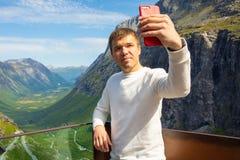 Jonge mens die selfie op de kronkelige weg van Trollstigen, Noorwegen maken stock afbeeldingen