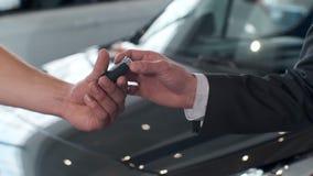 Jonge mens die sleutels van auto geven aan koper Mensen het schudden dient het mooie autohandel drijven op achtergrond van gekoch stock videobeelden