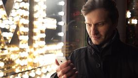 Jonge mens die smartphone op een stedelijke straat in avond gebruiken die bevinden zich dichtbij storefront stock videobeelden