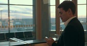 Jonge mens die sms in luchthaven typen