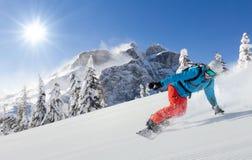 Jonge mens die snowboarder bergaf in Alpen lopen royalty-vrije stock foto