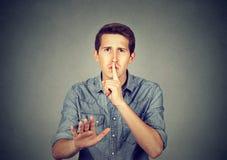 Jonge mens die stille Shhhh geven, stilte, geheim stock afbeelding