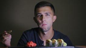 Jonge mens die sushi met eetstokjes eten stock footage