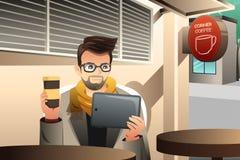 In jonge mens die tablet in een koffie gebruiken Stock Afbeelding