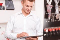 Jonge mens die tablet gebruiken bij boutique Stock Afbeeldingen