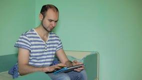 Jonge mens die tabletcomputer thuis met behulp van stock videobeelden