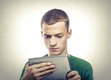 Jonge mens die tabletpc met behulp van stock afbeelding