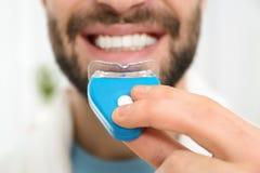 Jonge mens die tanden gebruiken die apparaat op lichte achtergrond witten stock fotografie