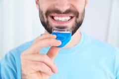 Jonge mens die tanden gebruiken die apparaat op lichte achtergrond witten royalty-vrije stock foto