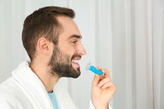 Jonge mens die tanden gebruiken die apparaat op lichte achtergrond witten stock foto's