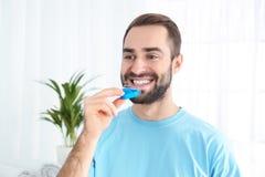 Jonge mens die tanden gebruiken die apparaat witten stock fotografie