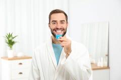 Jonge mens die tanden gebruiken die apparaat witten royalty-vrije stock afbeelding