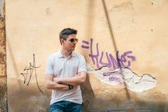Jonge mens die tegen de muur leunen stock fotografie
