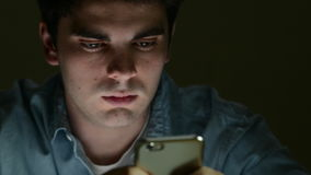 Jonge Mens die Tekstbericht op Mobiele Telefoon verzenden laat bij Nacht stock footage