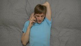 Jonge Mens die telefonisch op Bed roepen stock footage