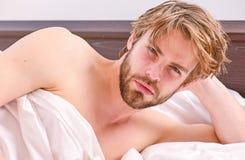 Jonge mens die terwijl ontwaken in de ochtend uitrekken zich Beeld die jonge mens het uitrekken in bed tonen zich Kielzog op ocht stock foto