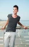 Jonge mens die terwijl op vakantie bij de kust glimlachen Royalty-vrije Stock Foto's