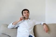 Jonge mens die thuis het roepen ontspannen door mobiele telefoon Royalty-vrije Stock Foto's