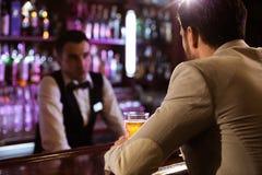 Jonge mens die tot drank opdracht geven aan een barman stock afbeelding