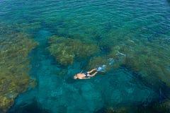Jonge mens die in transparante ondiepe oceaan snorkelen Royalty-vrije Stock Foto