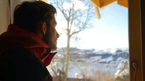 Jonge mens die uit het venster mooi landschap in de winter bekijken stock video