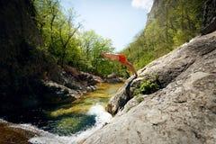 Jonge Mens die van Cliff Into Water van Bergrivier springen Stock Afbeelding