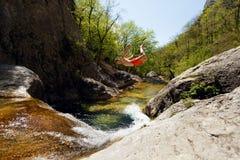 Jonge Mens die van Cliff Into Water van Bergrivier springen Royalty-vrije Stock Fotografie