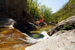 Jonge Mens die van Cliff Into Water van Bergrivier springen Royalty-vrije Stock Foto