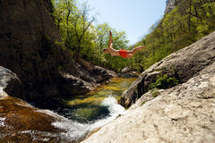Jonge Mens die van Cliff Into Water van Bergrivier springen Stock Foto's