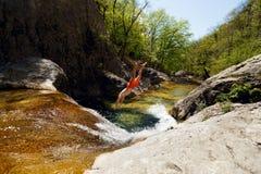 Jonge Mens die van Cliff Into Water van Bergrivier springen Stock Afbeeldingen