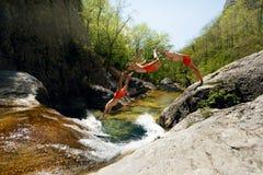 Jonge Mens die van Cliff Into Water van de Multiblootstelling van de Bergrivier springen Stock Afbeeldingen