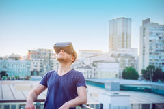 Jonge mens die van de virtuele hoofdtelefoon van werkelijkheidsglazen of 3d bril genieten die tegen stad de bouwachtergrond zich  Stock Foto
