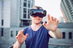 Jonge mens die van de virtuele hoofdtelefoon van werkelijkheidsglazen of 3d bril genieten die tegen moderne stad de bouwachtergro Stock Foto's
