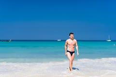 Jonge mens die van het water in een strand opstappen Stock Foto's