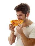 Jonge mens die van pizza geniet Royalty-vrije Stock Foto's