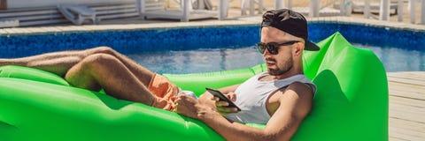 Jonge mens die van vrije tijd genieten, die op de luchtbank Lamzac liggen, dichtbij de poolbanner, LANG FORMAAT stock afbeelding