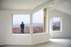 Jonge mens die van zijn nieuw huisbalkon kijkt Stock Foto