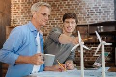 Jonge mens die verbeteringen in windturbines voorstellen stock fotografie