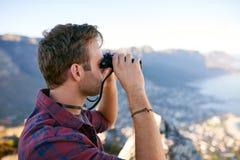 Jonge mens die verrekijkers aan een moutainkant met behulp van stock afbeeldingen