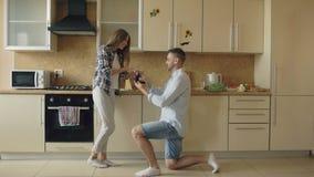 Jonge mens die voorstel thuis doen aan zijn meisje in de keuken stock videobeelden