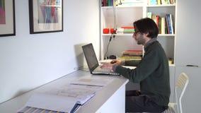 Jonge mens die in vrijetijdskleding in bureau werken stock footage