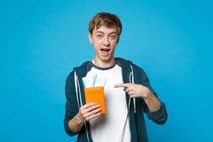 Jonge mens die in die vrijetijdskleding, richtend wijsvinger op paspoort, instapkaartkaartje houden op blauwe muur wordt geïsolee royalty-vrije stock foto