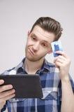 Jonge mens die wat denken om op Internet te kopen royalty-vrije stock fotografie